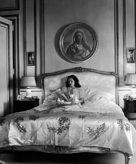 Subject: Socialite (debutante) Aileen Johnson Menocal eating breakfast in bed. Painting above her is supposedly her Mother painted as Madonna? Havana, Cuba 1946 Photographer- Nina Leen Time Inc Owned Merlin-1153830